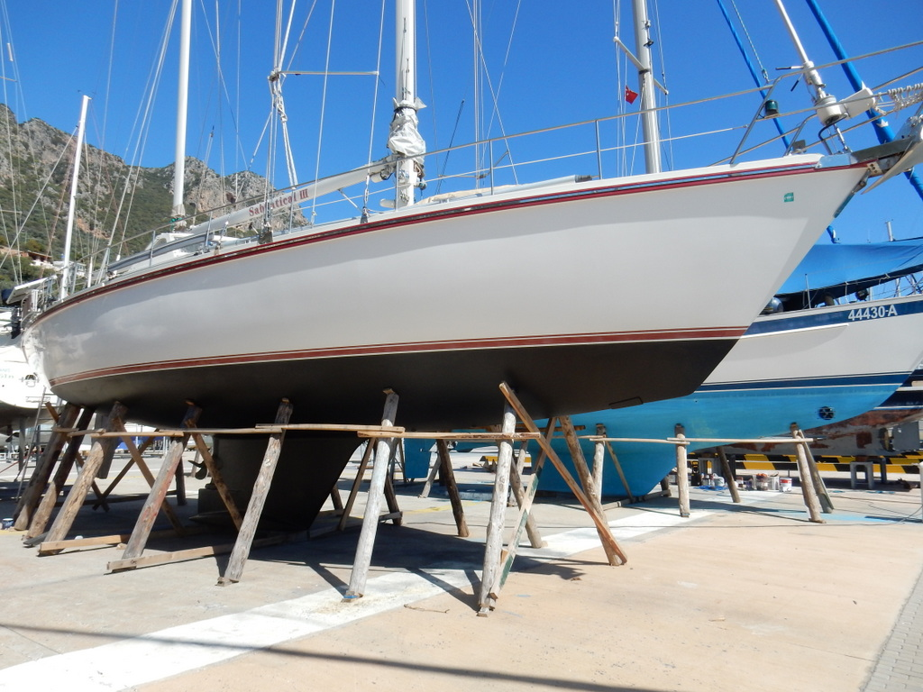 Sabbatical III shows off her waxed and polished topsides and new anti-fouling paint below the water line.  Note the timbers used to hold her up.