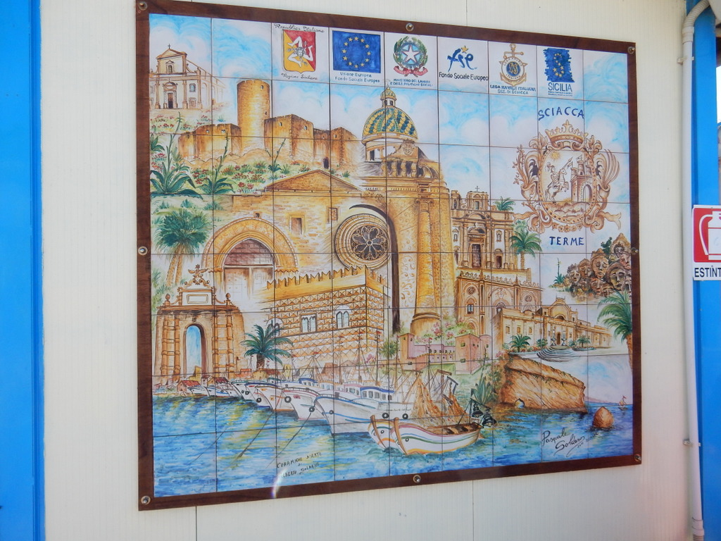 The Lega Navale dock as pictured in painted ceramic tiles. The building behind the boats are in the town center located up a steep hill from the marina.